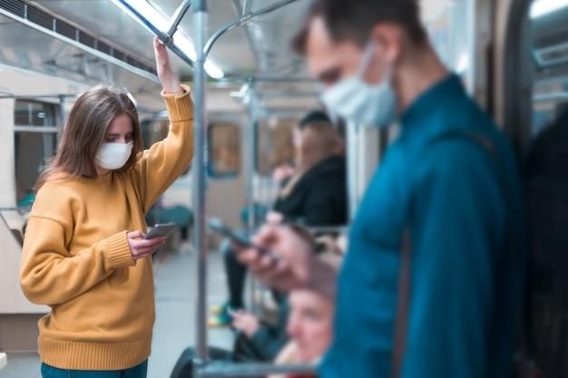地下鉄の車の中に立っている保護マスクの若い女性。市内のコロナウイルス