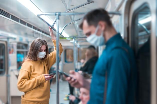 Молодая женщина в защитной маске, стоя в вагоне метро. коронавирус в городе