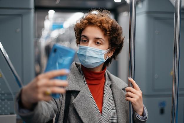 地下鉄の車内で自撮りをしている防護マスクを着た若い女性