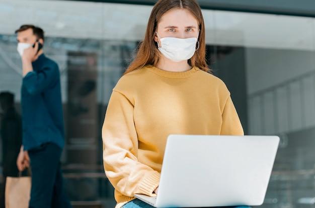 保護マスクをした若い女性が路上でラップトップを使用しています。健康保護の概念
