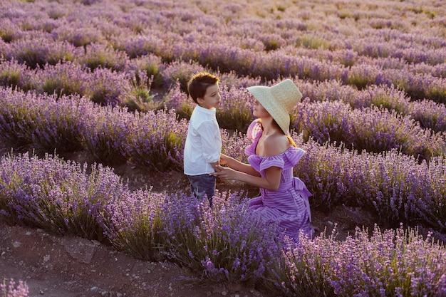 Молодая женщина в фиолетовом коротком платье и соломенной шляпе стоит в поле с лавандой в крыму на закате