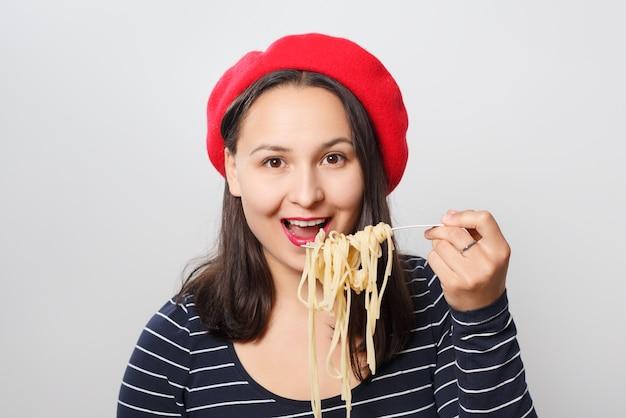 Молодая женщина в красном берете ест спагетти крупным планом.