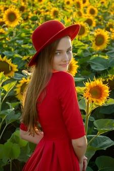 日の出のひまわりとフィールドで赤いドレスと帽子の若い女性