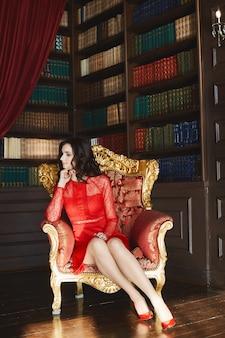 赤いドレスと赤い靴の若い女性はゴールドのヴィンテージアームチェアに座って、ライブラリのインテリアでポーズ