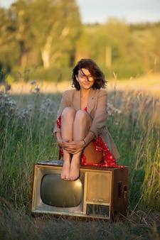 自然の中で古いレトロなテレビの上に座って赤いドレスの若い女性
