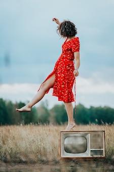 自然の中で古いレトロなテレビの上を歩く赤いドレスの若い女性
