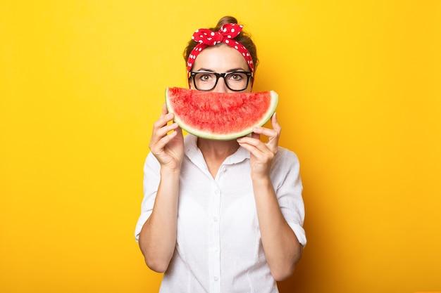 Молодая женщина в красной повязке и очках закрывает половину лица арбузом на желтой стене.