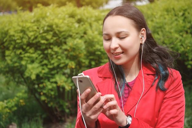 赤いジャケットを着た若い女性が、屋外のヘッドフォンでスマートフォンから音楽を聴く