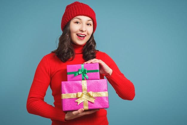 クリスマスプレゼントと赤いセーターとキャップの若い女性。青い背景に。