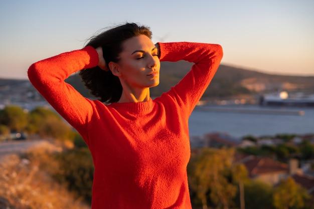 Молодая женщина в красном свитере на великолепном закате на горе