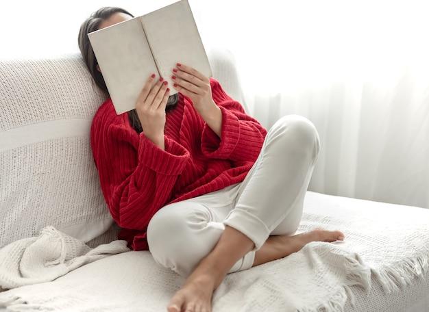 彼女の手で本を持って自宅のソファで赤いセーターを着た若い女性。