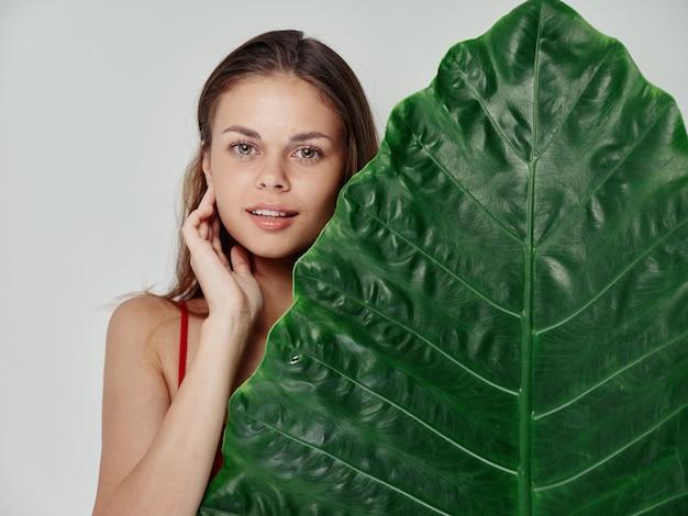 明るい背景にヤシの木の緑の葉と赤いtシャツの若い女性