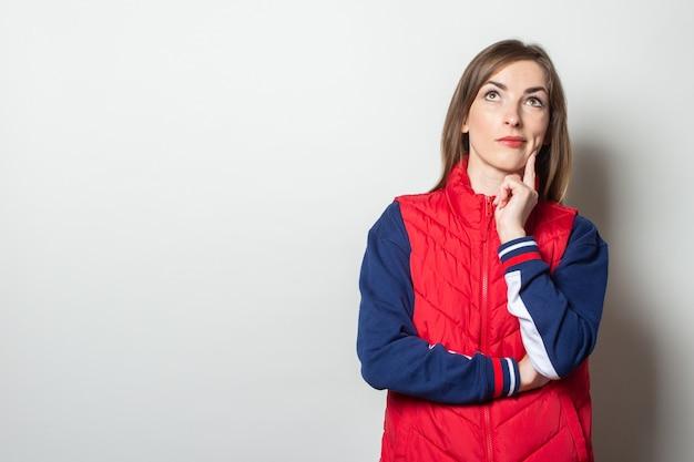 Молодая женщина в красном жилете в задумчивой позе смотрит вверх на фоне светлой стены
