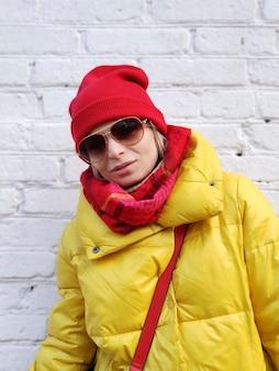 Молодая женщина в красно-желтом модном образе в солнечных очках на поверхности белой кирпичной стены.