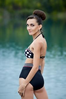 屋外でポーズレトロな水着の若い女性