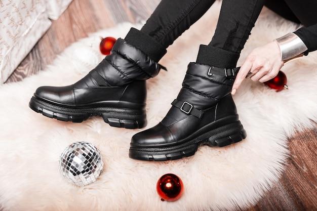 Молодая женщина в комнате на белом пушистом ковре среди новогодних игрушек сидит и измеряет кожаные модные черные сапоги