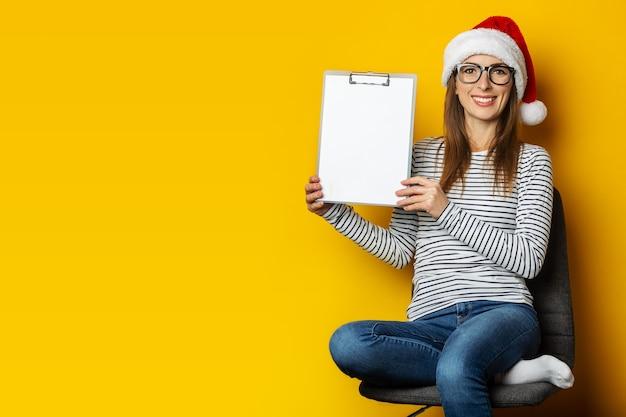 サンタの帽子をかぶった若い女性が椅子に座ってクリップボードを保持します。