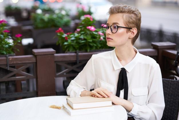 カフェのテーブルで本とシャツとメガネの若い女性