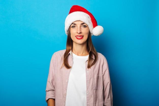 Молодая женщина в рубашке в шляпе санта-клауса