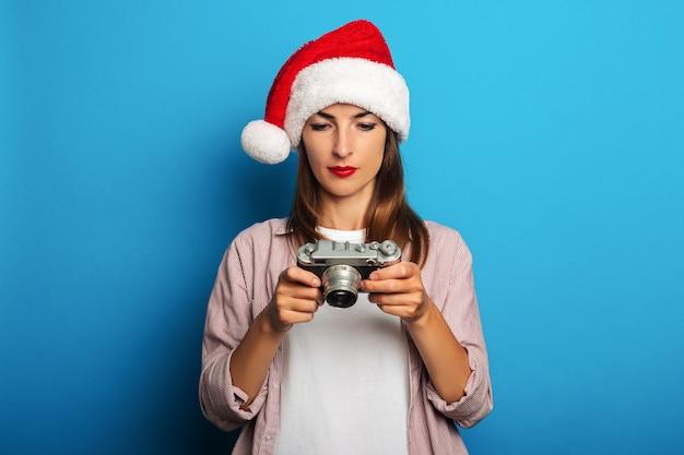 サンタクロースの帽子をかぶったシャツを着た若い女性