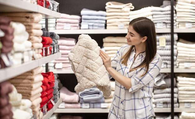 Молодая женщина в магазине выбирает текстиль.