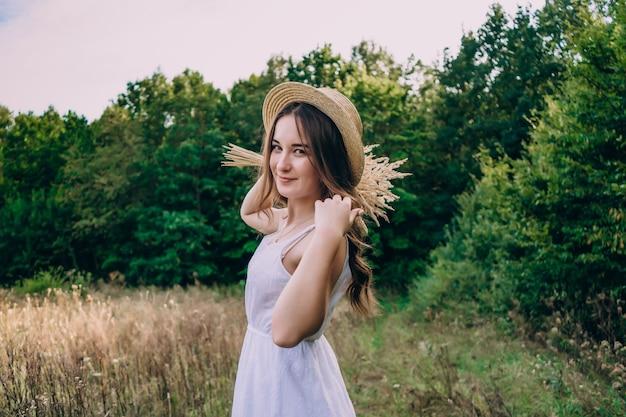 키 큰 허브의 배경에 밀짚 모자에 젊은 여자. 필드에 말린 꽃의 꽃다발과 드레스에 아름 다운 소녀.