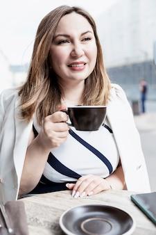 Молодая женщина в уличном кафе с чашкой. улыбающаяся брюнетка. вертикальный.