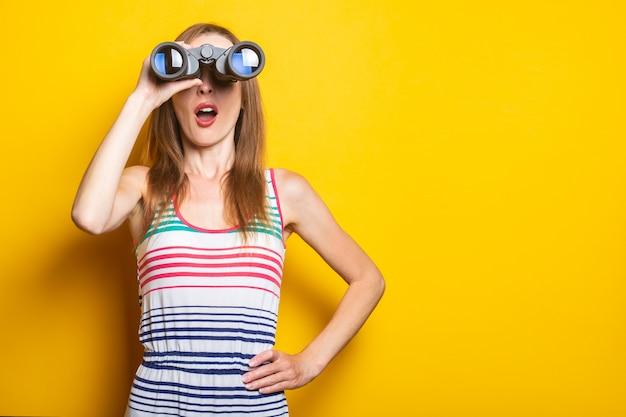 Молодая женщина в полосатом платье в шоке от удивления смотрит в бинокль на желтом пространстве