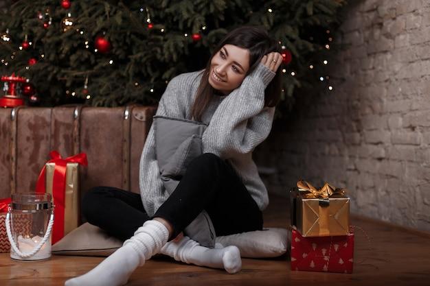 흰색 양말에 검은 바지에 세련된 빈티지 스웨터를 입은 젊은 여성이 선물 중 크리스마스 아늑한 방에서 크리스마스 트리 근처 바닥에 앉아 있습니다. 귀여운 소녀는 휴일에 대해 생각합니다.