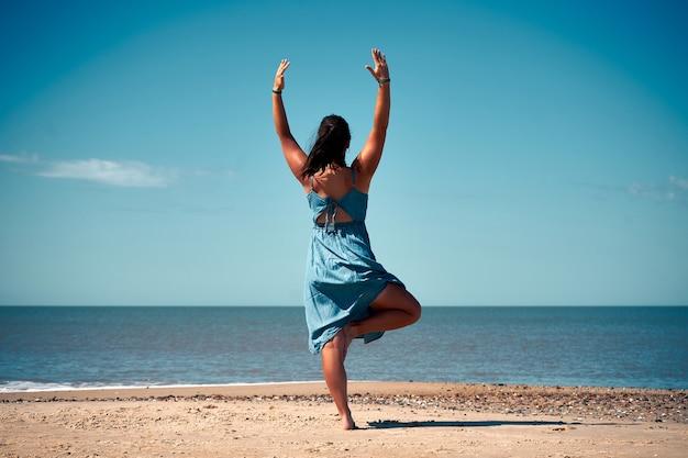 Молодая женщина в летнем платье делает упражнения йоги на песчаном пляже