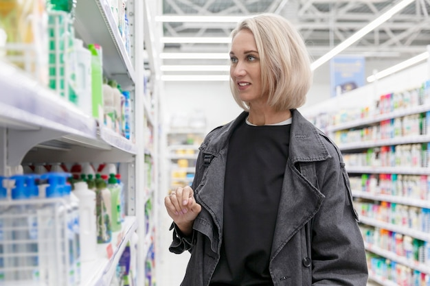 슈퍼마켓에서 젊은 여자는 청소 제품을 선택합니다.