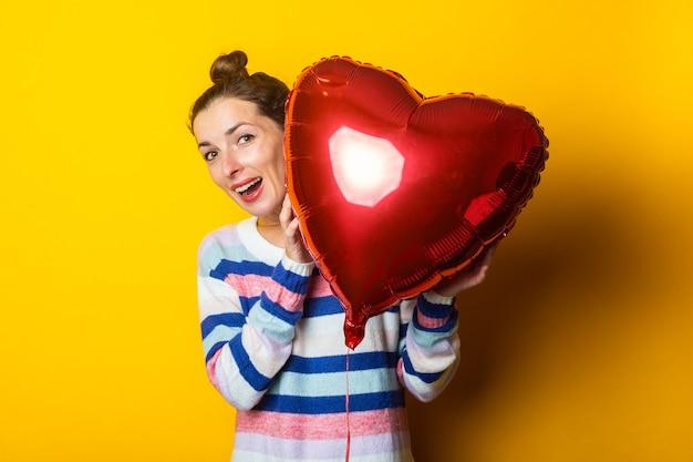 セーターを着た若い女性は、黄色の背景に気球のハートの後ろに隠れています。バレンタインデーの作文。