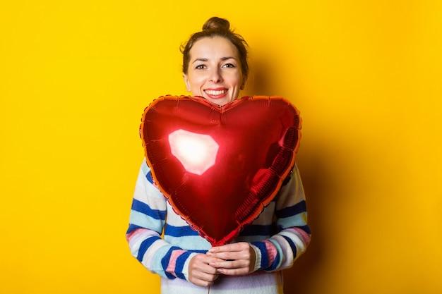 セーターを着た若い女性は、黄色の背景に気球のハートを保持しています。バレンタインデーの作文。