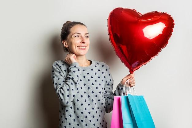 스웨터를 입은 젊은 여성이 기뻐하고 밝은 배경에 쇼핑 패키지와 심장 공기 풍선을 보유하고 있습니다. 발렌타인 데이 개념. 배너.