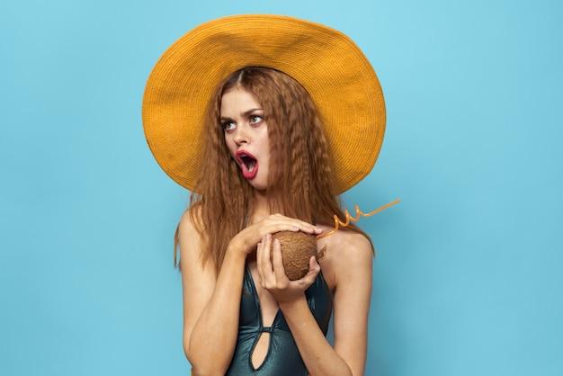 水着の若い女性とパイナップルを手にスタジオで帽子