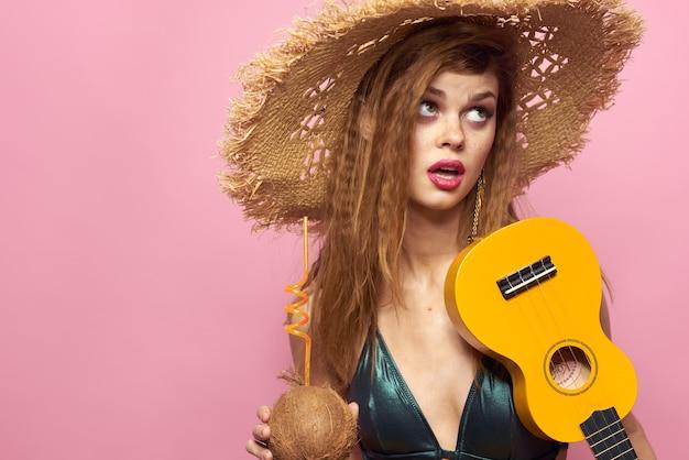 Молодая женщина в купальнике и шляпе играет на гитаре укулеле