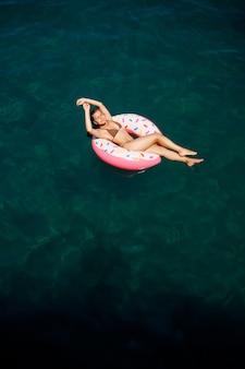 水着姿の若い女性が海の膨脹可能なリングで泳ぎます。夏休みのコンセプト。