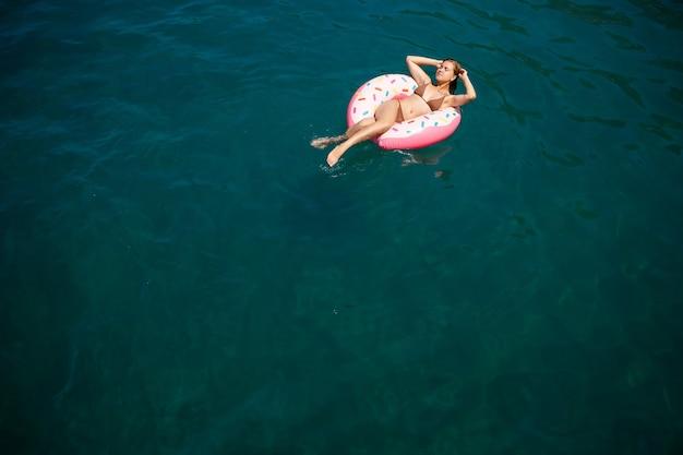 Молодая женщина в купальнике плавает на надувном кольце в море. концепция летних каникул.