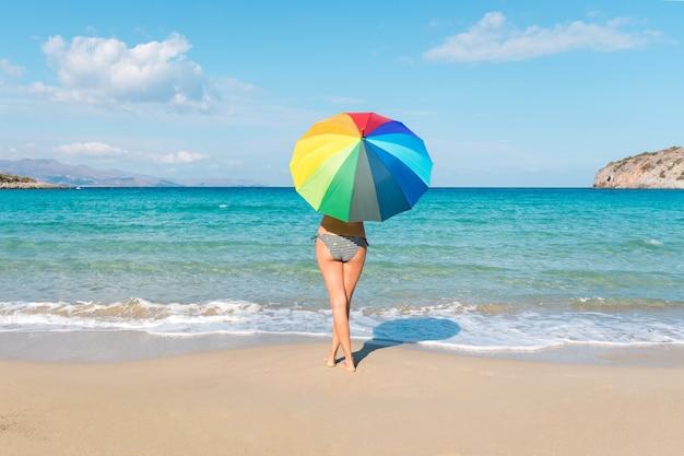 Молодая женщина в купальнике с красочным зонтиком на пляже
