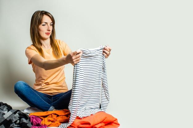 Tシャツとジーンズの若い女性は、明るい背景に床に座って物事を選択します