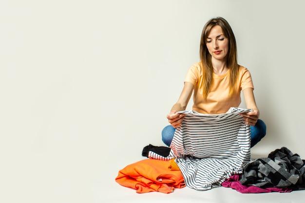 Молодая женщина в футболке и джинсах выбирает вещи, сидя на полу на светлом фоне