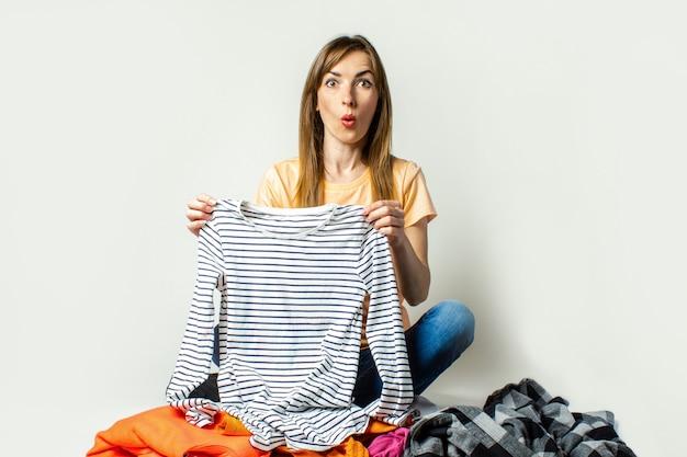 Tシャツとジーンズの若い女性が床に座っている間ワードローブのものを選択します