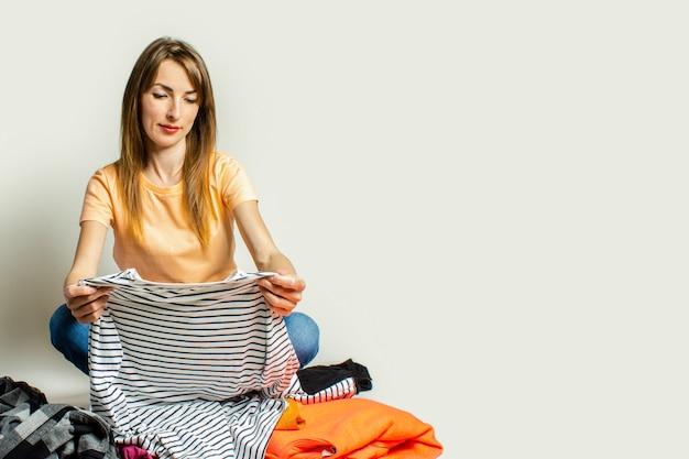 Молодая женщина в футболке и джинсах выбирает гардеробные вещи, сидя на полу