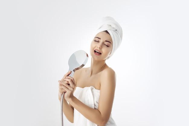 シャワーヘッドを保持しているタオルの若い女性
