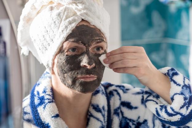 Молодая женщина в полотенце делает косметическую маску дома в ванной.