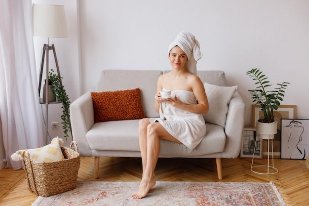 週末にリビングルームでお茶とタオルで若い女性