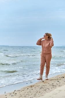 海岸沿いの砂の上を歩いて空を見ているフードを着て、トラックスーツを着た若い女性