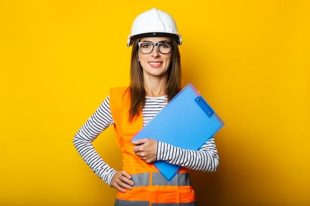 ベストとヘルメットをかぶった若い女性は、黄色の背景にクリップボードを保持しています。建設コンセプト、新しい建物。バナー。