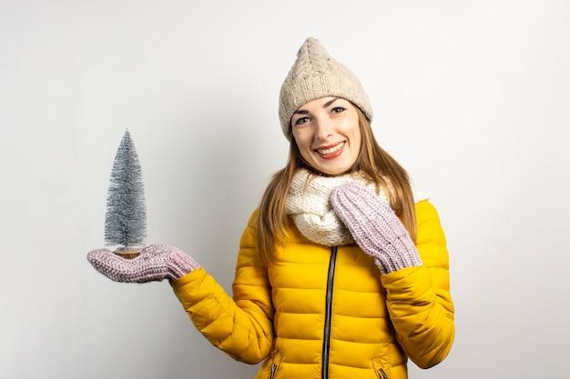 Молодая женщина в теплой шапке и варежках улыбается изолированными