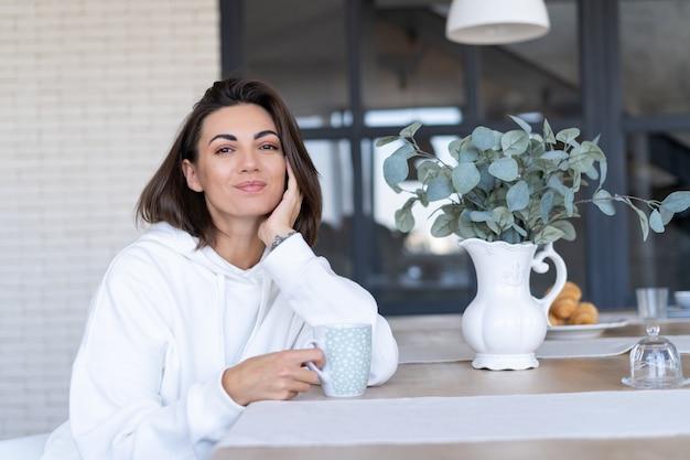 Молодая женщина в теплой белой толстовке с капюшоном дома на кухне начинает свой день с чашки кофе